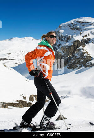 Famale sking doing snowsports on a snow mountain in Val D'Isere with an orange jacket on a sunny day - Stock Photo