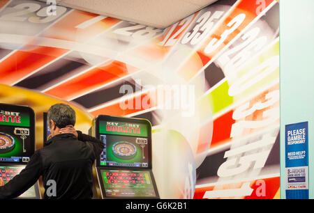 Mature man using fixed odds betting machine in Bookmakers. England, UK. - Stock Photo
