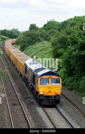 GBRf Class 66 diesel locomotive pulling an empty stone ballast train, Warwickshire, UK - Stock Photo