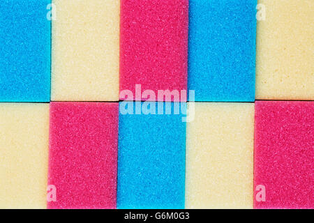 Colored kitchen sponges arranged in a row. Ware washing theme. Absorbent material. Abstract scene. - Stock Photo