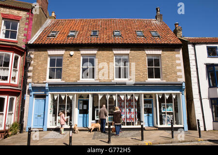 UK, England, Yorkshire, Staithes, High Street, customers looking in Staithes Gallery window - Stock Photo