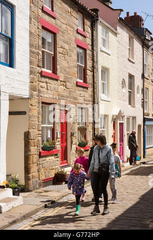 UK, England, Yorkshire, Staithes, High Street, family walking on cobbles - Stock Photo