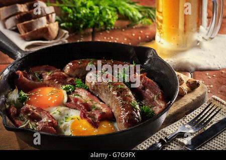 Male brutal dinner of fried sausages, bacon, scrambled eggs on the background of beer, herbs and bread. - Stock Photo