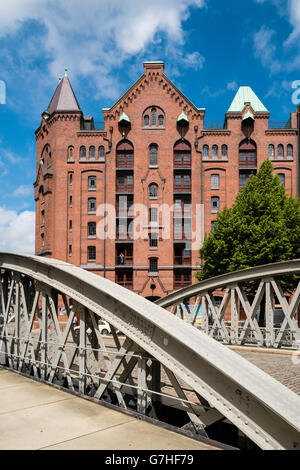 View of historic red brick warehouses and bridge at Speicherstadt beside canals in Hamburg Germany - Stock Photo