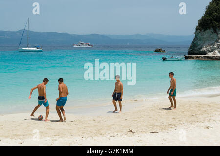 group of young men playing football on beautiful sandy Vrika beach, on the tiny island Antipaxos, Ionian Islands, - Stock Photo