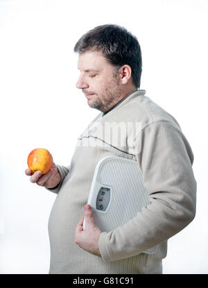 Adult men holding bathroom scale looking at a healthy apple. Staying healthy and loosing weight - Stock Photo