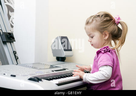 Little cute baby girl playing at synthesizer at home - Stock Photo