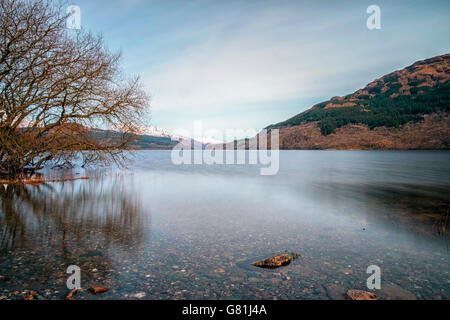 Long exposure of calm waters of Loch Lomond with snow covered mountains in the distance - Stock Photo
