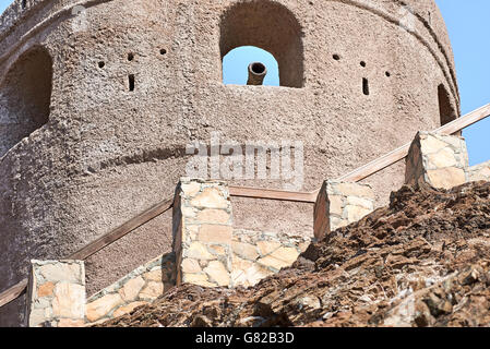 Watch tower of a fort with a cannon in the ramparts against a blue sky - Stock Photo
