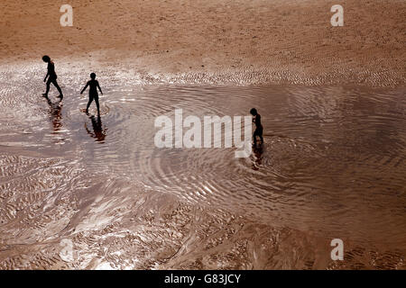 Three silhouetted children paddling in the early evening, San Sebastian, Spain - Stock Photo