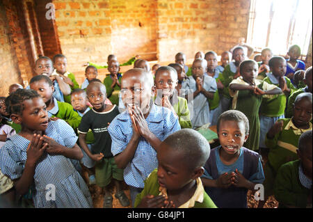 Group  of Ugandan school children in a rural African school gather for morning preys, looking focused and anxious - Stock Photo