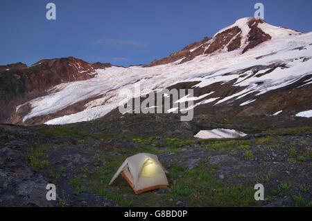 Tent illuminated at dusk on climbers camp on slopes of Heliotrope Ridge, Mount Baker Wilderness North cascades Washington - Stock Photo