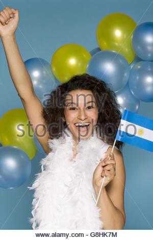 Hispanic woman cheering with Argentine Flag - Stock Photo