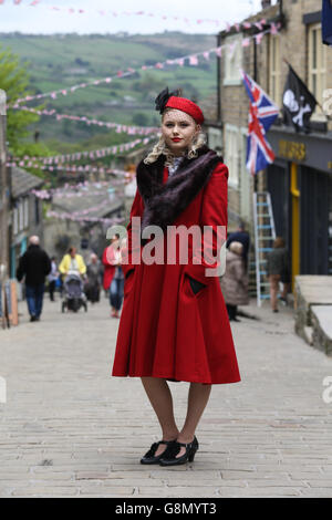 Kirsty Garwood, wearing 1940s attire, poses on the bunting draped street during the annual 1940's weekend in Haworth, - Stock Photo
