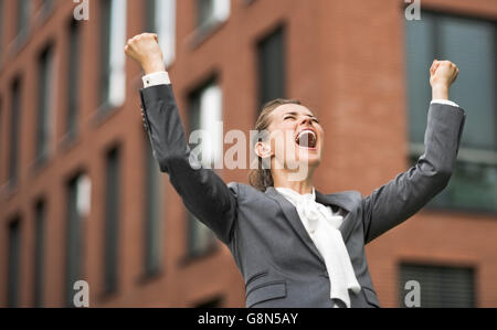 The new business. Happy modern business woman against office building rejoicing - Stock Photo