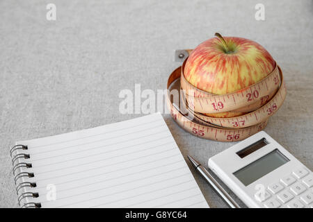 Apple, tape measure, notebook and calculator background for diet plan, weight loss plan - Stock Photo