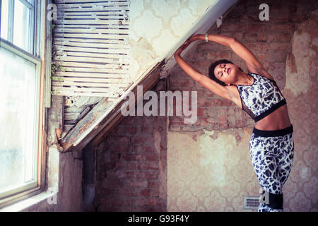 Beauty in dereliction : Fitness and fashion photography of a young afro-caribbean girl  exercising in a derelict - Stock Photo