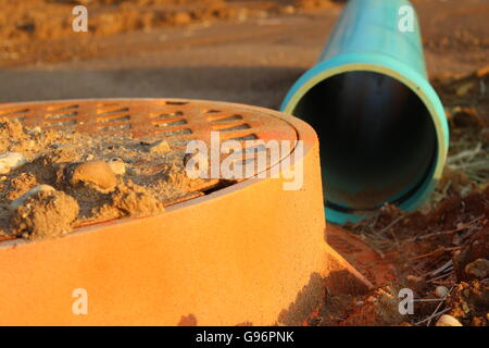 An Orange Man Hole Next to Blue Pipe in Dirt in New Housing Development - Construction in the Neighborhood - Stock Photo