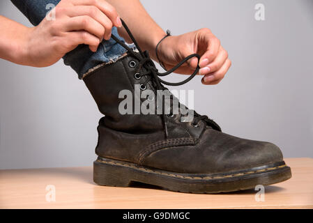 Woman's hand lacing up a black leather boot - Stock Photo