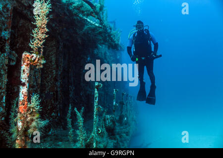 Scuba diver hovers near the deck of a sunken patrol boat. - Stock Photo