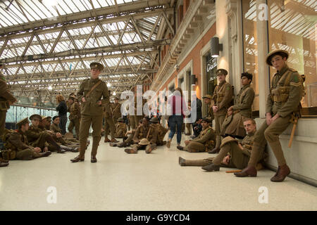 London, UK. 1st July, 2016. A silent tribute by men dressed as First World War Soldiers at Waterloo Station to mark - Stock Photo