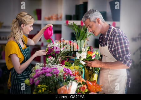 Female florist watering flowers - Stock Photo