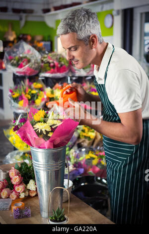 Male florist watering flowers with watering can - Stock Photo