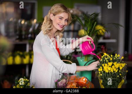 Happy female florist watering flowers - Stock Photo