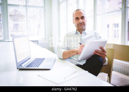 Businessman writing on document - Stock Photo
