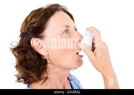 Close-up of mature woman using asthma inhaler - Stock Photo