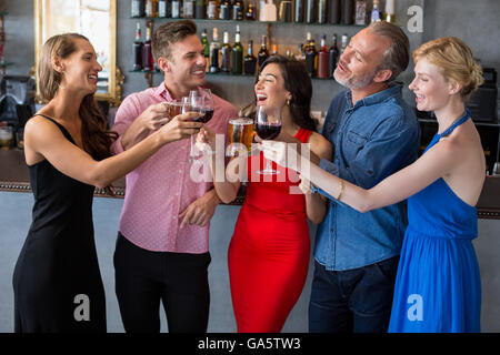 Group of friends toasting glasses of beer and wine - Stock Photo