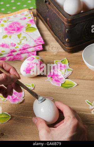 Apply woman PVA glue on colored Easter egg, with the technique of decoupage - Stock Photo