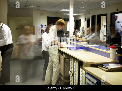 Ward reception in a busy general hospital, showing doctors, nurses and medical staff blurred as they move quickly - Stock Photo