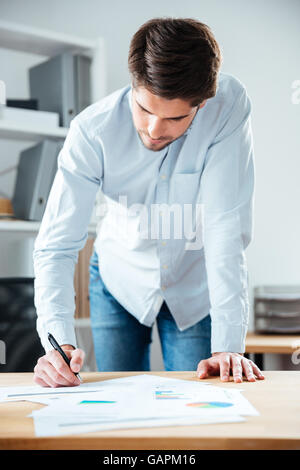 Serious young businessman staning and writing on the table in office - Stock Photo