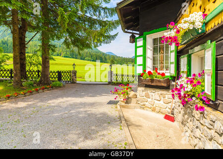 WEISSENSEE LAKE, AUSTRIA - JUL 6, 2015: windows decorated with flowers of a typical alpine house in countryside - Stock Photo