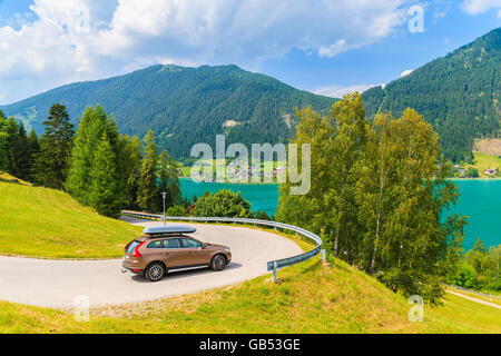 Car on scenic mountain road driving along Weissensee lake in summer landscape of Carinthia region, Austria - Stock Photo