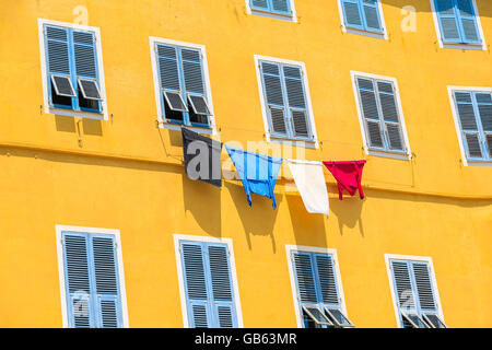 Laundry hanging out of a typical Corsican house facade in Bastia town, Corsica island, France - Stock Photo