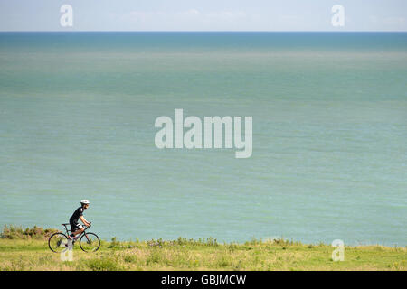 Man on a cyclocross bike cycling on a cliff top path in the South Downs National Park at Cuckmere haven, near Eastbourne - Stock Photo