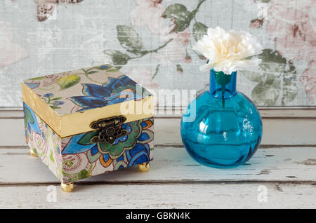A handmade gilded trinket box with vase and flower on a shabby chic background - Stock Photo