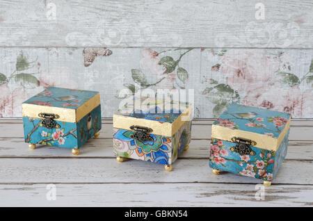 Handmade decoupaged trinket boxes on a shabby chic background - Stock Photo