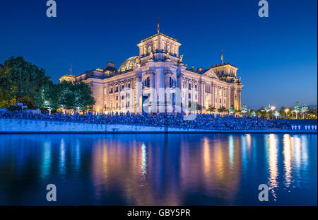 Classic view of famous Reichstag building reflecting in Spree river in twilight during blue hour at dusk, Berlin, - Stock Photo