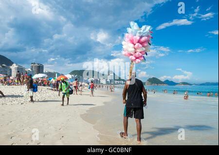 RIO DE JANEIRO - FEBRUARY 27, 2016: Brazilian beach vendor selling cotton candy floss approaches potential customers, - Stock Photo
