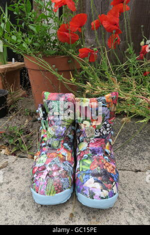 Walking boots, re-purposed as garden containers and decorated with images from a gardening catalogue, using decoupage - Stock Photo