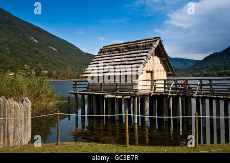 Replica of wooden house with thatched roof on stilts, lake Revine, Cansiglio plateau, Treviso, Veneto, Italy, Europe - Stock Photo