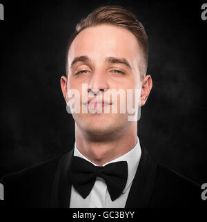 Highly successful business man in suit over dark background. - Stock Photo