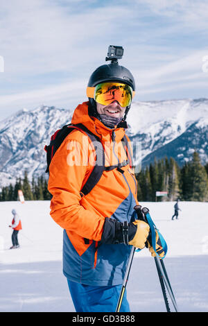 A man in orange ski jacket, with a head cam and helmet. - Stock Photo