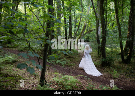 A young blonde woman girl wearing an old-fashioned white wedding dress frock walking alone  in a woodland on a summer - Stock Photo