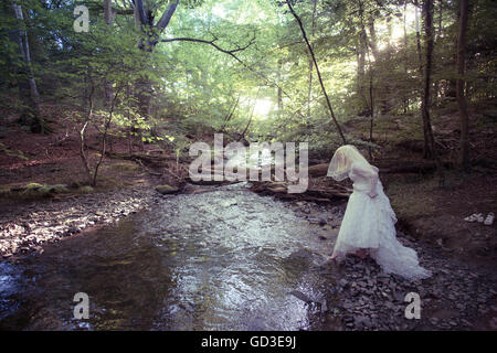 A young blonde woman girl wearing an old-fashioned white wedding dress frock walking alone  by a stream in a woodland - Stock Photo