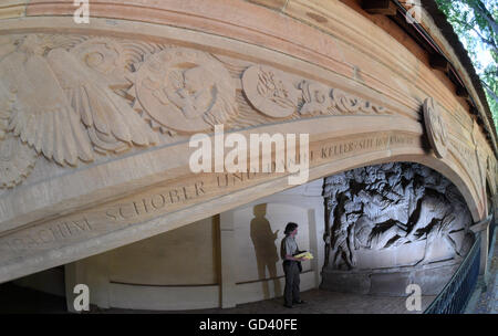 A man looking at a wall relief in a restored arcade arch at Stadtgottesacker in Halle/Saale, Germany, 12 July 2016. - Stock Photo