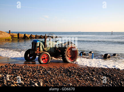 A tractor with boat trailer in the sea after launch of inshore fishing boat at Cromer, Norfolk, England, United - Stock Photo